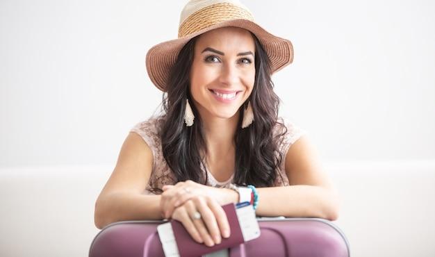 아름다운 여성 여행자는 시세표와 여권을 손에 들고 모자를 쓰고 얼굴에 미소를 띠고 짐을 들고 비행기를 탈 준비가 되어 있습니다.