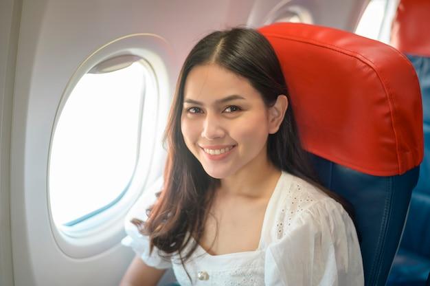 Красивая женщина-путешественница использует смартфон в самолете