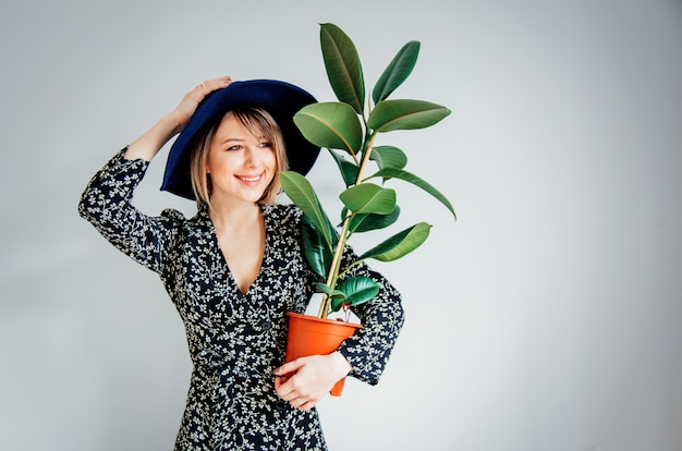 Beautiful woman in trendy dress with plant in a pot