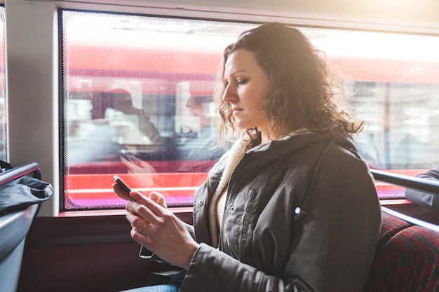 Beautiful woman typing on smart phone while commuting in london