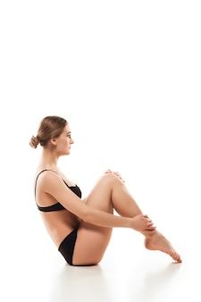 Bella donna in biancheria intima isolata sul pavimento bianco