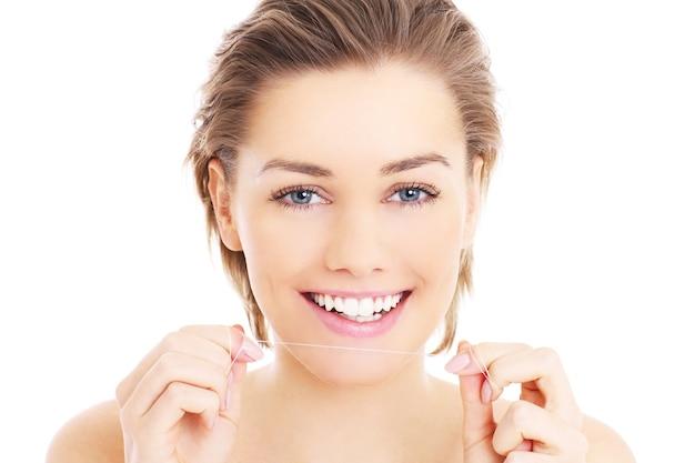 白い背景の上の彼女の歯にデンタルフロスを使用して美しい女性
