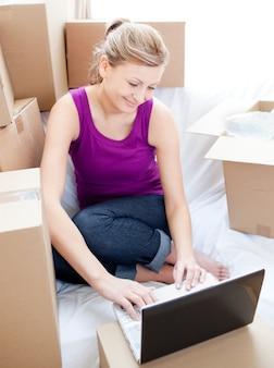 상자를 풀고있는 동안 노트북을 사용 하여 아름 다운 여자