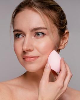 Красивая женщина с помощью блендера для макияжа