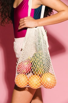 과일을 살 때 그물 가방을 사용하는 아름다운 여성