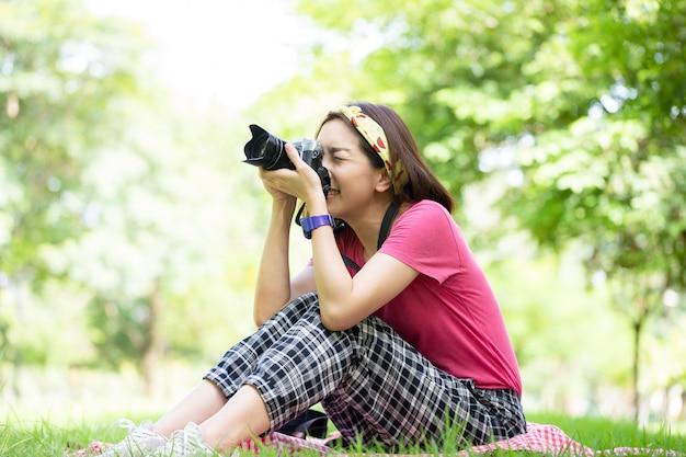 아름다운 여자가 카메라를 사용하고 공공 공원에서 사진을 찍고, 아침에 행복한 느낌으로 건강한 몸 자세