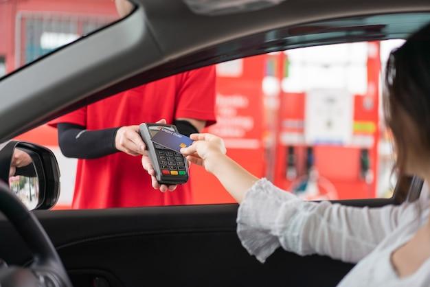 주유소에서 지불 휘발유 연료 보급을 위해 카드 결제 단말기와 신용 카드를 사용하는 아름다운 여자
