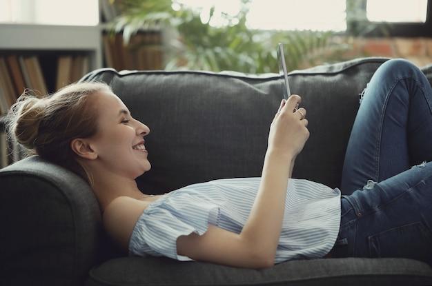 Beautiful woman using digital tablet, lying on sofa