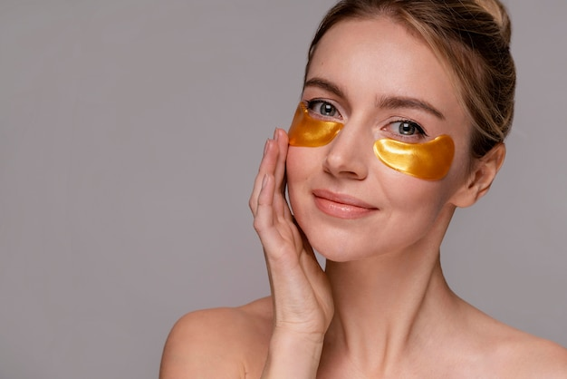 Beautiful woman using under eyes patches