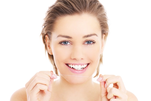 Beautiful woman using a floss for her teeth over white background