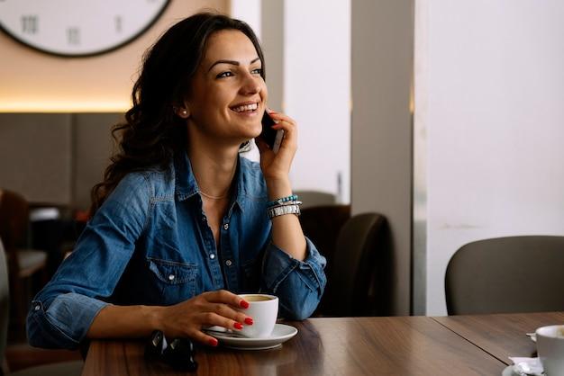 コーヒーショップで彼女の携帯電話を使用している美しい女性。