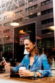 Красивая женщина, используя свой мобильный телефон в кафе.