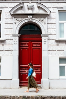 街を歩きながら携帯を使っている美女。
