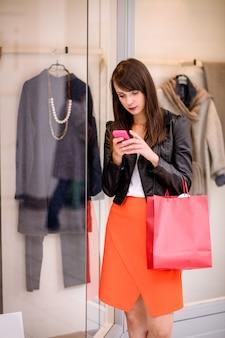 Beautiful woman using her phone while window shopping