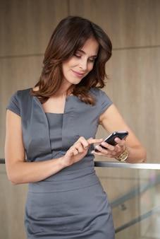 Bella donna che utilizza il suo telefono al lavoro