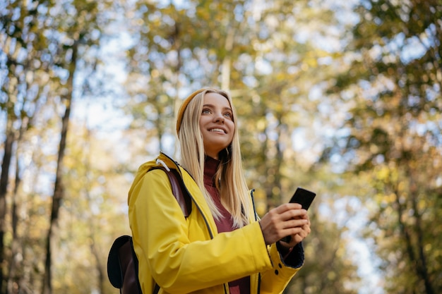 Beautiful woman using mobile application to navigate in autumn forest