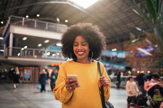 駅で携帯を使っている美女。コミュニケーションの概念。