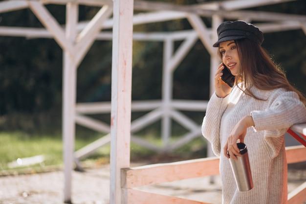 Bella donna utilizzando il telefono e bere il tè