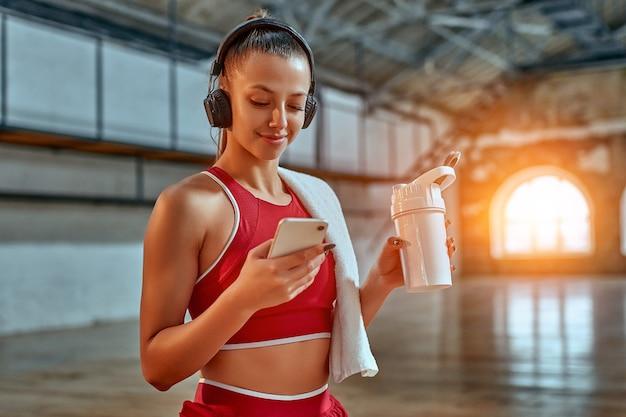 スマートフォンを使用し、ヘッドフォンで音楽を聴いている美しい女性は、フィットネスルームで運動しながらプロテインシェイクを飲みます。スポーツとテクノロジーのコンセプト。