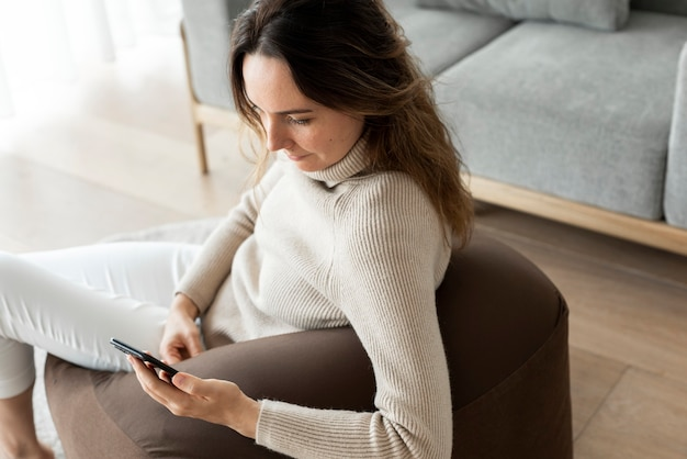 Beautiful woman using smartphone on a couch