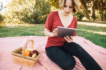 Beautiful woman using tablet on picnic