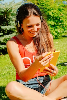 Beautiful woman using tablet outdoors.