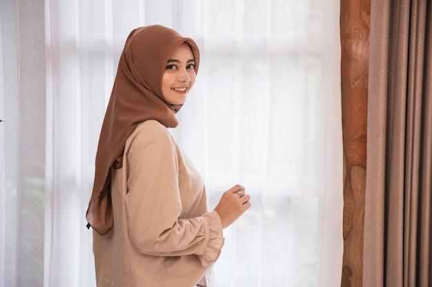 振り返ってみると笑顔のカーテンの近くに立っている美しい女性ベール