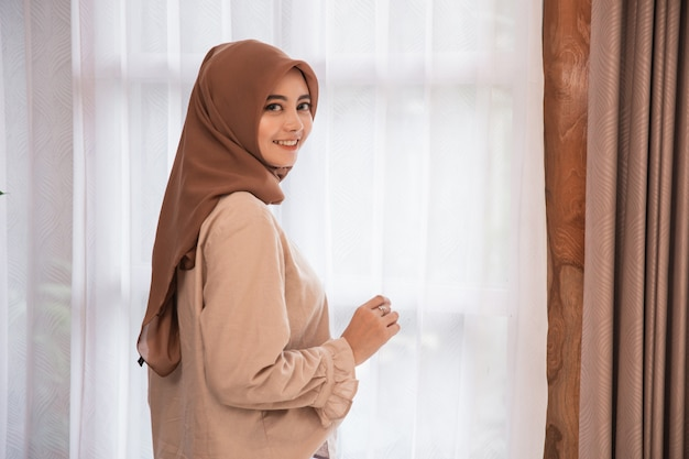 Beautiful woman veiled standing near curtain looking back and smiling