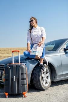 여행에 대 한 아름 다운 여자보기지도입니다. 차 옆에 서있는 예쁜 여자. 여행의 즐거움