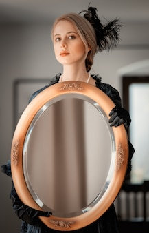 Beautiful woman in vintage black dress holding a mirror in indoor