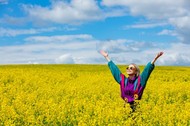 Beautiful woman in vintage tracksuit in yellow rapeseed field