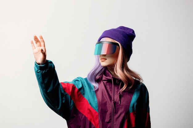 Beautiful woman in vr glasses and 80s sport suit on white background