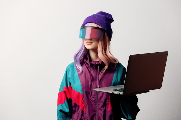 Beautiful woman in vr glasses with laptop and 80s sport suit on white background