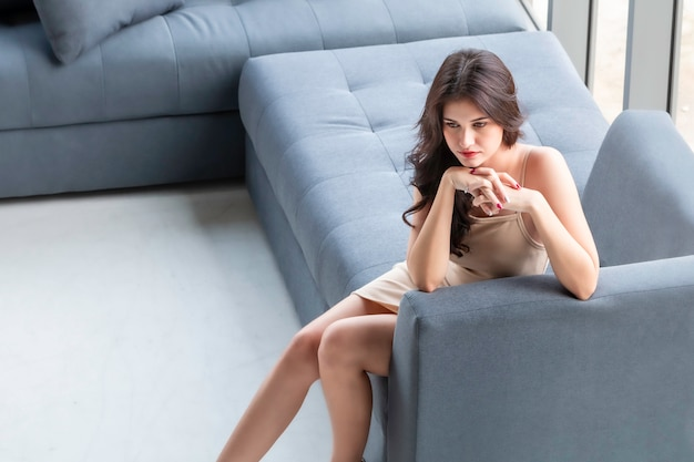 Beautiful woman waiting and thinking ideal on living room.