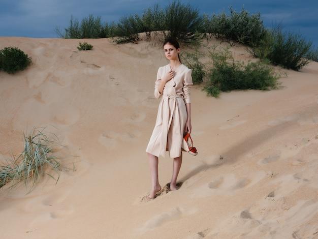 美しい女性は、ビーチの砂の熱帯のエレガントなスタイルに沿って歩きます