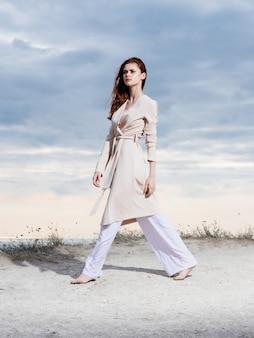 美しい女性がビーチに沿って歩く砂熱帯ライフスタイルファッション