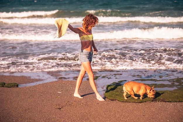 바다와 함께 해변에서 산책하는 아름다운 여성과 모래에 강아지와 함께 - 자유의 여인 혼자 그리고 휴가에 고립