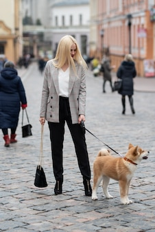 Beautiful woman walking her dog in the city during the day, akita, businesswoman.