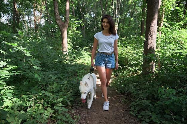 Красивая женщина гуляет со своей собакой