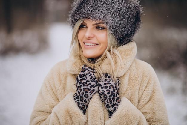 눈이 가득한 공원에서 산책하는 아름 다운 여자
