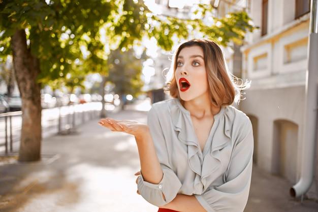 赤いスカートの屋外エンターテイメントを歩く美しい女性