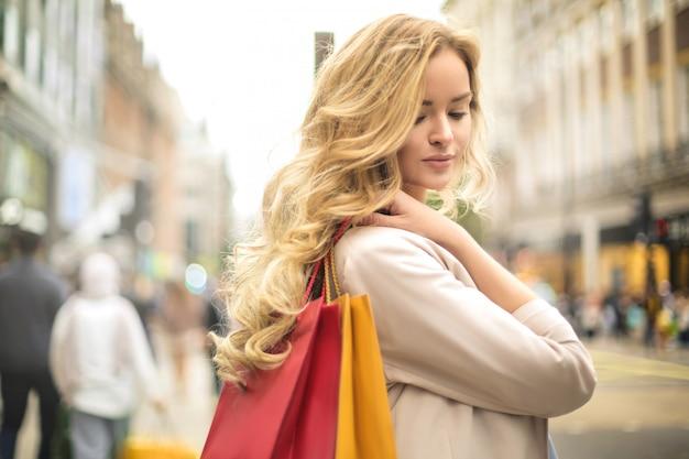 Красивая женщина идет по улице, перевозящих сумки