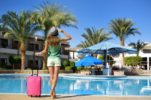 Beautiful woman walking near hotel pool area with pink suitcase