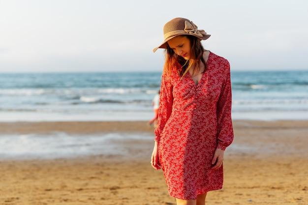 帽子と赤いドレスを着て春にビーチを歩く美しい女性。イースター休暇のコンセプト。スペイン