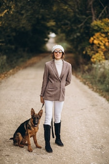 Beautiful woman walking out her dog in autumn park