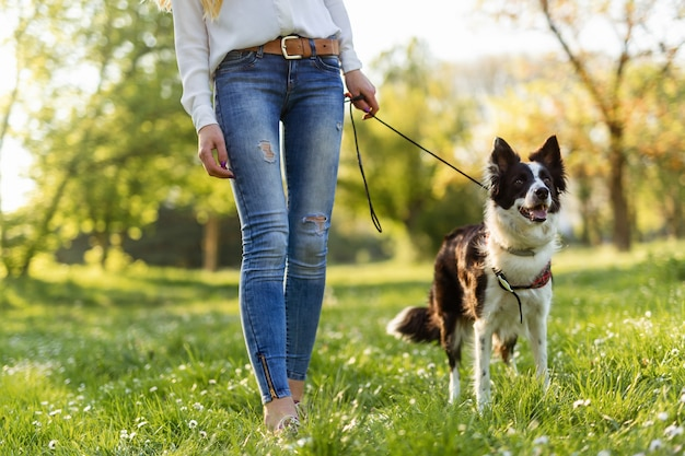 아름다운 여성이 걷고, 야외에서 귀여운 강아지와 놀고 있습니다.
