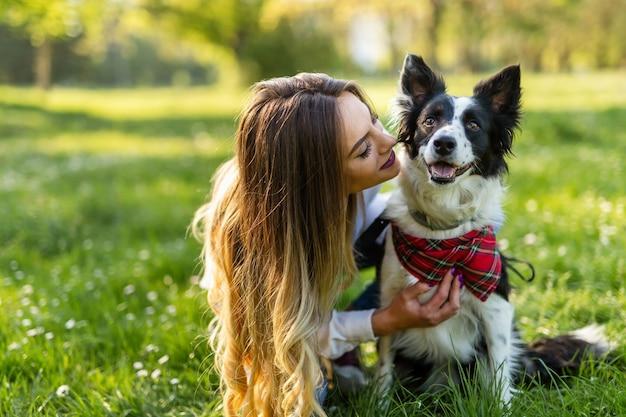 自然の中で屋外でかわいい犬と遊んで歩いている美しい女性