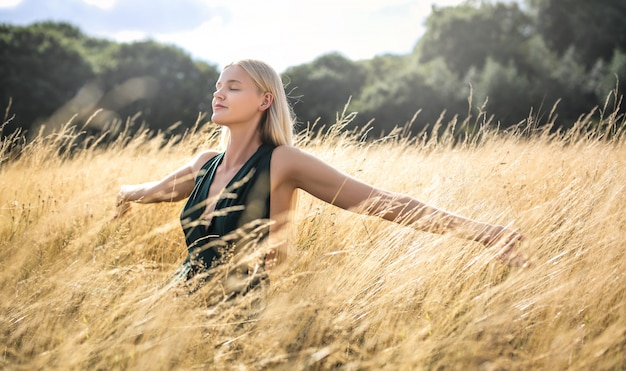 Beautiful woman walking in a wheat field and breathing deep