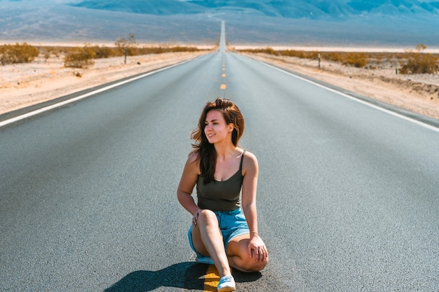 美しい女性は、アメリカの山々を見下ろすデスバレーの絵のように空っぽの道路に沿って歩く