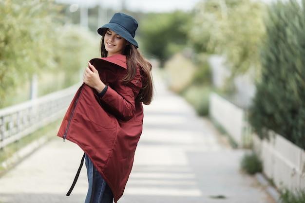 美しい女性が秋のコートを着て路地を歩きます。